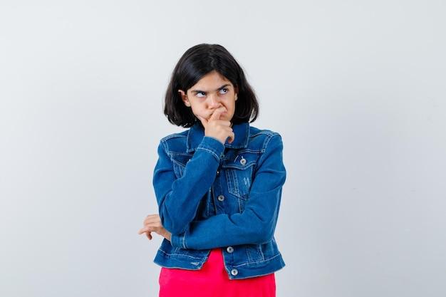 Młoda dziewczyna w czerwonej koszulce i dżinsowej kurtce opierając podbródek na dłoni, myśląc o czymś i patrząc zamyślony, widok z przodu.