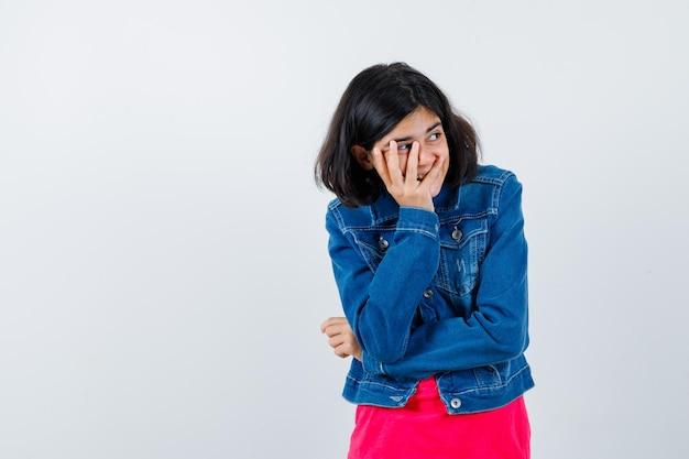 Młoda dziewczyna w czerwonej koszulce i dżinsowej kurtce, opierając policzek pod ręką, odwracając wzrok i patrząc podekscytowany, widok z przodu.