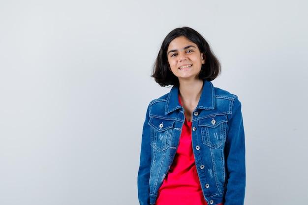 Młoda dziewczyna w czerwonej koszulce i dżinsowej kurtce stojąca prosto i pozująca do kamery i wyglądająca na szczęśliwą