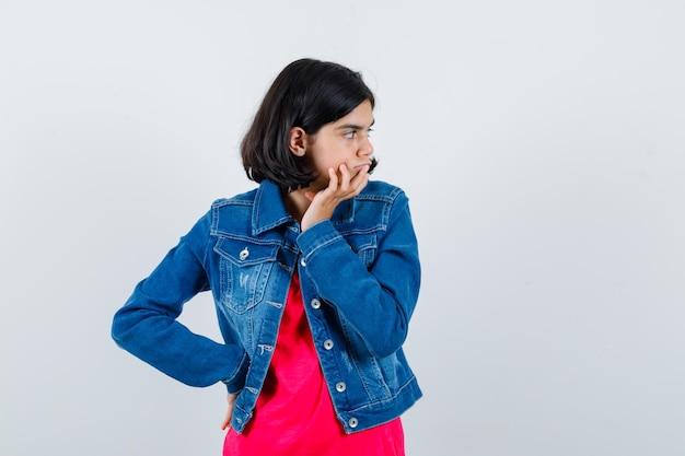 Młoda dziewczyna w czerwonej koszulce i dżinsowej kurtce stojąca w myśleniu pozie i patrząc zamyślony, widok z przodu.