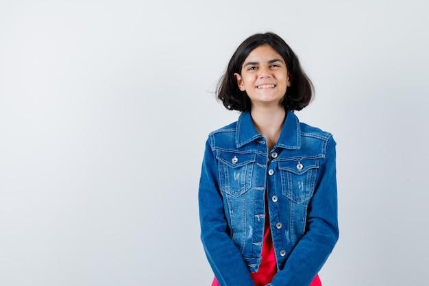 Młoda dziewczyna w czerwonej koszulce i dżinsowej kurtce stojący prosto i pozowanie na aparat i patrząc szczęśliwy, widok z przodu.