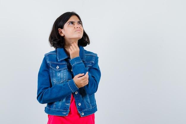 Młoda dziewczyna w czerwonej koszulce i dżinsowej kurtce, trzymając rękę na łokciu i patrząc powyżej i patrząc zamyślony, widok z przodu.