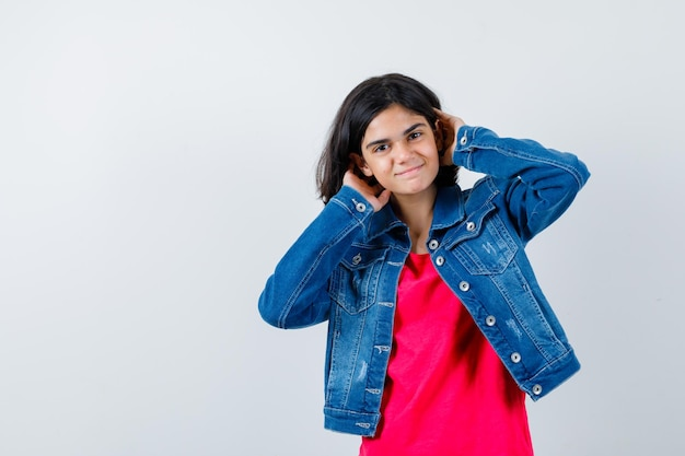 Młoda dziewczyna w czerwonej koszulce i dżinsowej kurtce trzymająca się za ręce za głową i wyglądająca na szczęśliwą