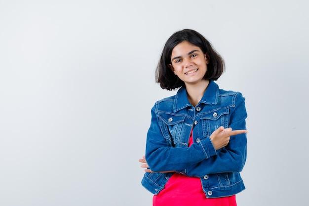 Młoda dziewczyna w czerwonej koszulce i dżinsowej kurtce wskazująca w prawo i wyglądająca na szczęśliwą