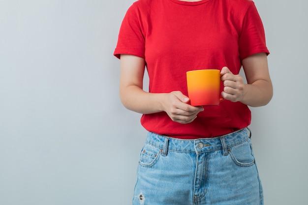 Młoda dziewczyna w czerwonej koszuli trzymająca filiżankę napoju