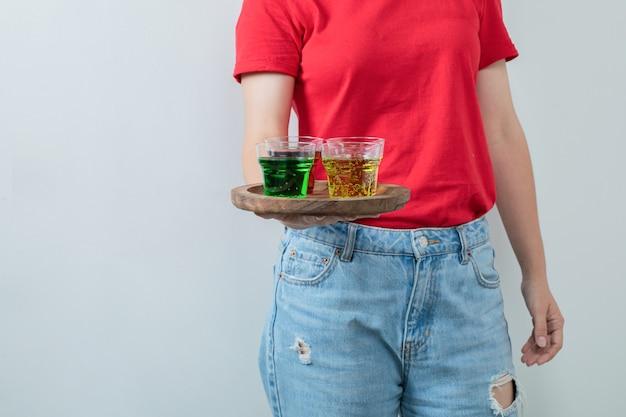 Młoda dziewczyna w czerwonej koszuli trzymająca półmisek z napojami