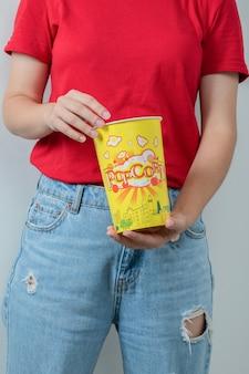 Młoda dziewczyna w czerwonej koszuli trzymająca pudełko popcornów