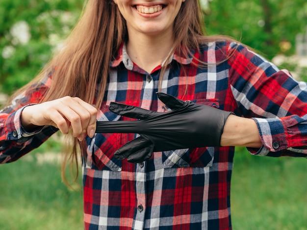 Młoda dziewczyna w czerwonej koszuli w kratkę zdejmuje czarne lateksowe rękawiczki