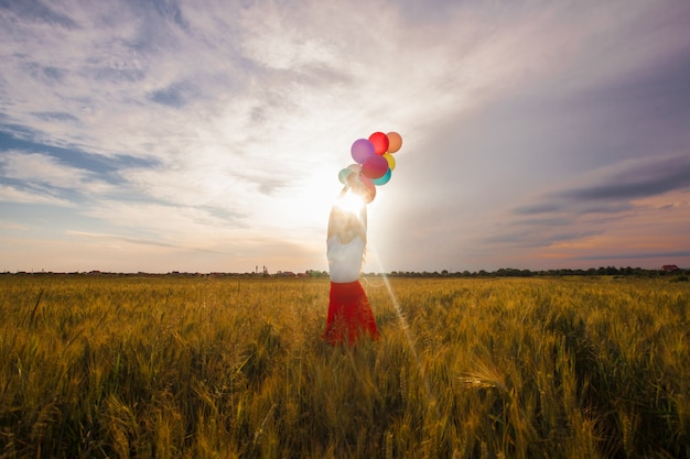 Młoda dziewczyna w czerwonej spódnicy z kolorowymi balonami w polu pszenicy. inspiracje naturą, podświetlenie