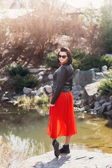 Młoda dziewczyna w czerwonej sukience stoi w pobliżu jeziora. kobieta pozuje w naturze