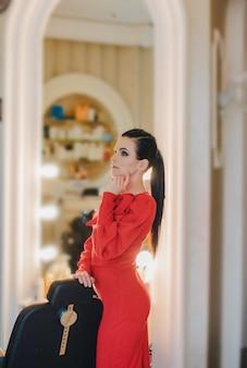 Młoda dziewczyna w czerwonej sukience w pomieszczeniu. zamyślony model. dziewczyna w salonie piękności.