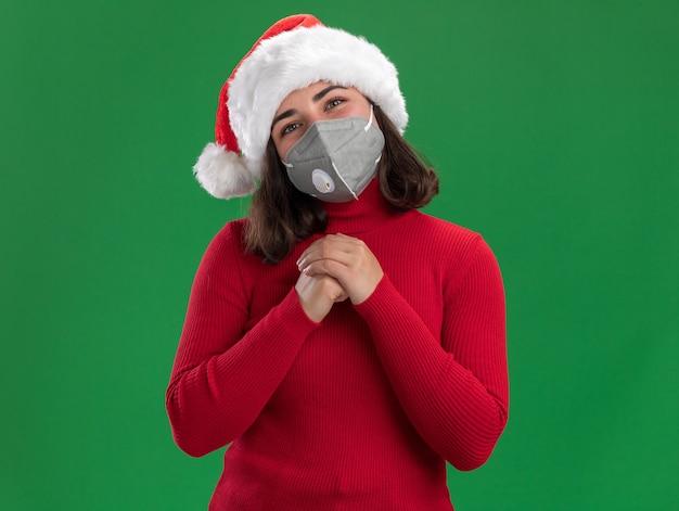 Młoda dziewczyna w czerwonym swetrze i kapeluszu mikołaja na sobie maskę ochronną na twarz z szczęśliwą twarzą, trzymając się za ręce razem, czekając na niespodziankę stojącą nad zieloną ścianą