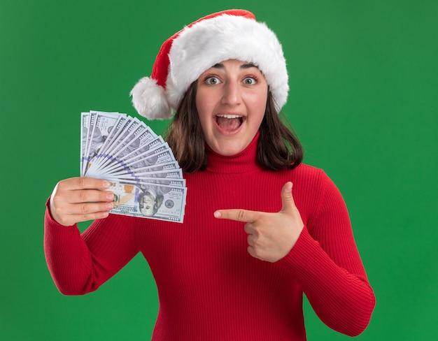 Młoda dziewczyna w czerwonym swetrze i santa hat trzyma gotówkę, wskazując palcem wskazującym na pieniądze, szczęśliwa i zaskoczona stojąc nad zieloną ścianą