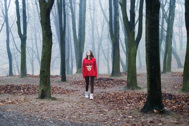 Młoda dziewczyna w czerwonym swetrze idzie sama po zimnym, mglistym lesie