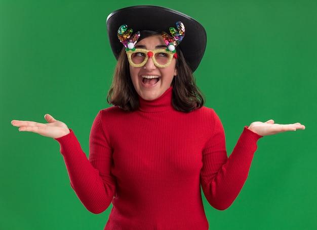 Młoda dziewczyna w czerwonym swetrze na sobie śmieszne okulary i czarny kapelusz patrząc na kamery szczęśliwa i pozytywna