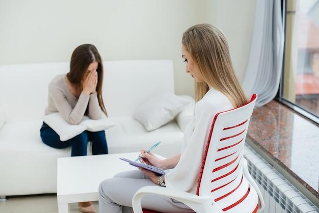 Młoda dziewczyna w depresji komunikuje się z psychologiem w gabinecie
