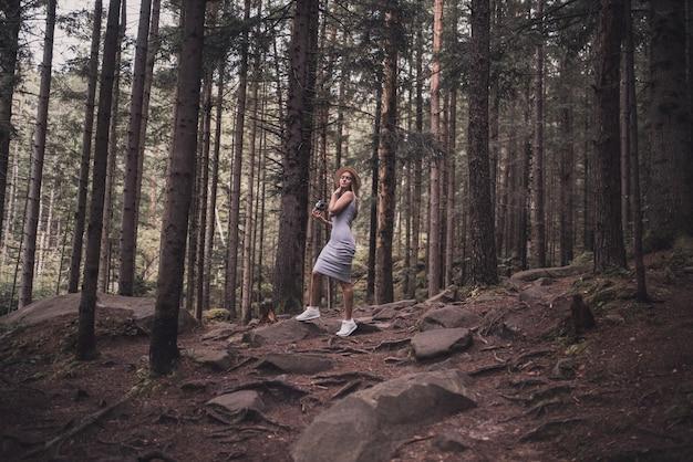 Młoda dziewczyna w długiej sukni stojącej w lesie