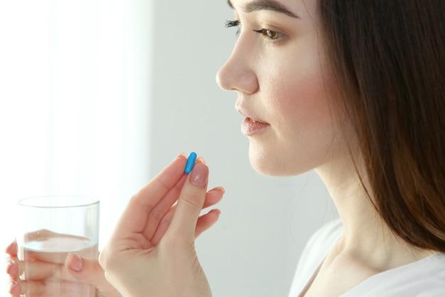 Młoda dziewczyna w dobrym nastroju bierze tabletki w domu