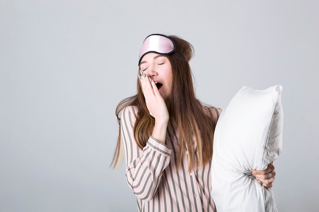 Młoda dziewczyna w dobrym nastroju w piżamie z poduszką na jasnym tle