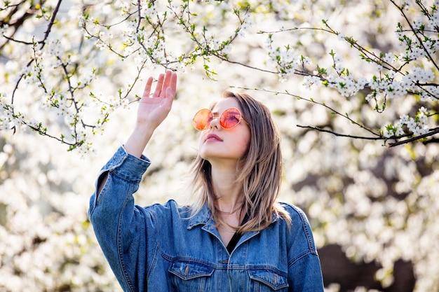 Młoda dziewczyna w drelichowej kurtce i okularach przeciwsłonecznych stoi blisko kwiatonośnego drzewa