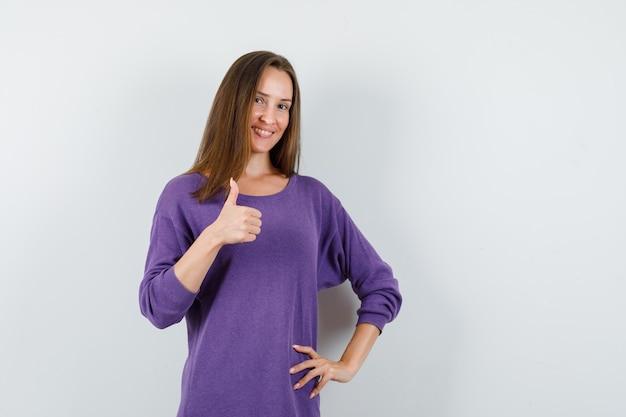 Młoda dziewczyna w fioletowej koszuli pokazując kciuk i patrząc wesoło, widok z przodu.