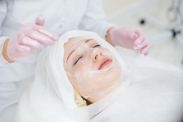 Młoda dziewczyna w gabinecie kosmetologicznym przechodzi zabiegi odmładzające skórę twarzy. kosmetyka.