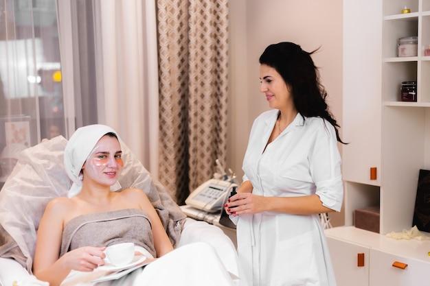 Młoda dziewczyna w gabinecie kosmetycznym w gabinecie kosmetologicznym leży na łóżku relaksuje się z maską