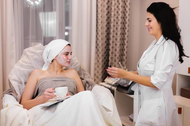 Młoda dziewczyna w gabinecie kosmetycznym w gabinecie kosmetycznym leży na łóżku relaksuje się z maską na twarzy