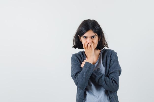 Młoda dziewczyna w jasnoszarym t-shircie i ciemnoszarej bluzie z kapturem na suwak kładzie dłoń na ustach, pozuje do kamery i wygląda uroczo