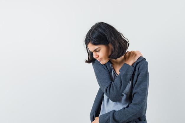 Młoda dziewczyna w jasnoszarym t-shircie i ciemnoszarej bluzie z kapturem z zamkiem błyskawicznym kładzie rękę na ramieniu, odczuwa ból ramienia i wygląda na wyczerpaną
