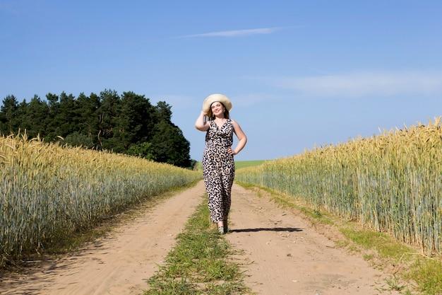 Młoda dziewczyna w kapeluszu idzie wiejską piaszczystą drogą, słoneczna, jasna letnia pogoda, posuwa się naprzód po polu żyta z żółtym żytem
