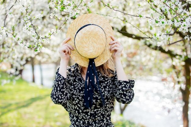 Młoda dziewczyna w kapeluszu pobyt blisko kwitnącego drzewa