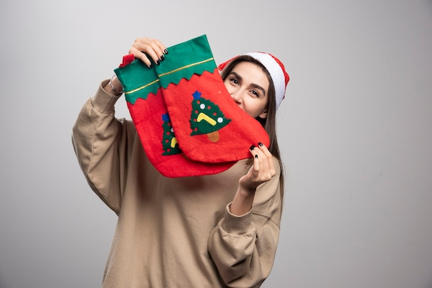 Młoda dziewczyna w kapeluszu świętego mikołaja, trzymając dwie świąteczne skarpetki.