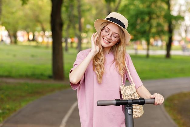 Młoda dziewczyna w kapeluszu ze skuterem w parku latem