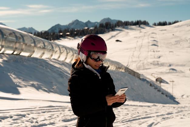 Młoda Dziewczyna W Kasku Narciarskim Konsultuje Swój Telefon Komórkowy W Ośrodku Narciarskim W Alpach Premium Zdjęcia