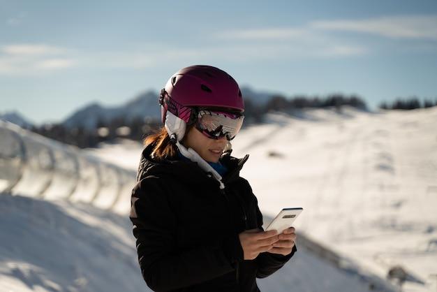Młoda dziewczyna w kasku narciarskim konsultuje swój telefon komórkowy w ośrodku narciarskim w alpach
