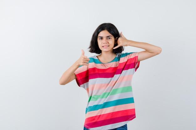 Młoda dziewczyna w kolorowe paski t-shirt pokazano zadzwoń do mnie gest i kciuk i patrząc ładny, widok z przodu.