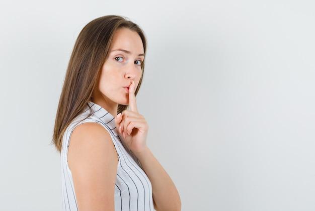 Młoda dziewczyna w koszulce pokazuje gest ciszy i wygląda rozsądnie.