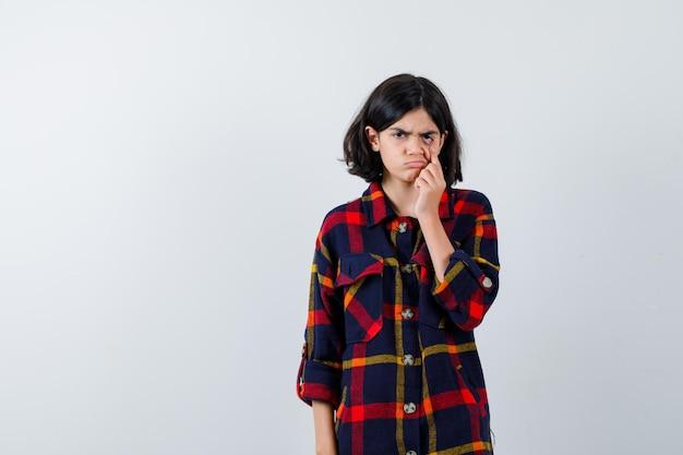 Młoda dziewczyna w kraciastej koszuli, ciągnąc w dół powiekę i patrząc zirytowaną, widok z przodu.