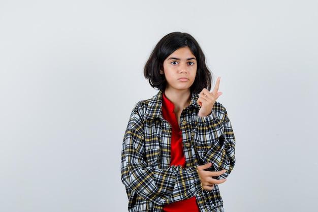 Młoda dziewczyna w kraciastej koszuli i czerwonej koszulce podnosząca palec wskazujący w geście eureka, trzymająca rękę na łokciu i wyglądająca rozsądnie, widok z przodu.