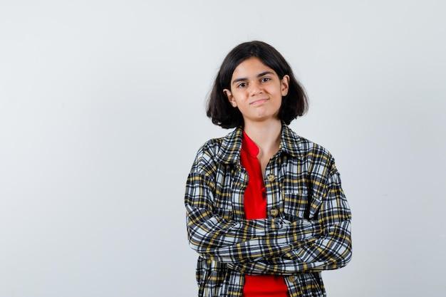 Młoda dziewczyna w kraciastej koszuli i czerwonej koszulce stojącej z rękami skrzyżowanymi i patrzącą na szczęśliwą, widok z przodu.