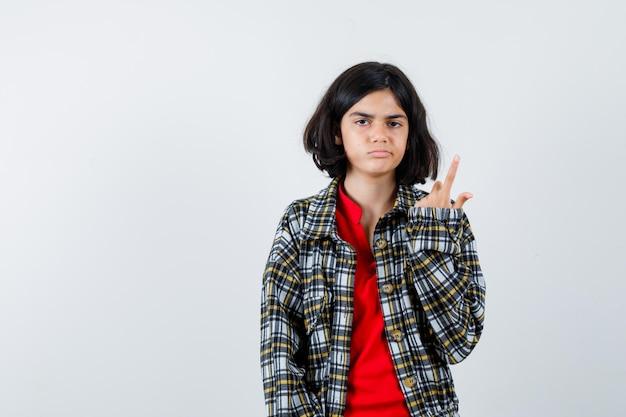 Młoda dziewczyna w kraciastej koszuli i czerwonej koszulce, wskazując w górę i patrząc poważnie, widok z przodu.