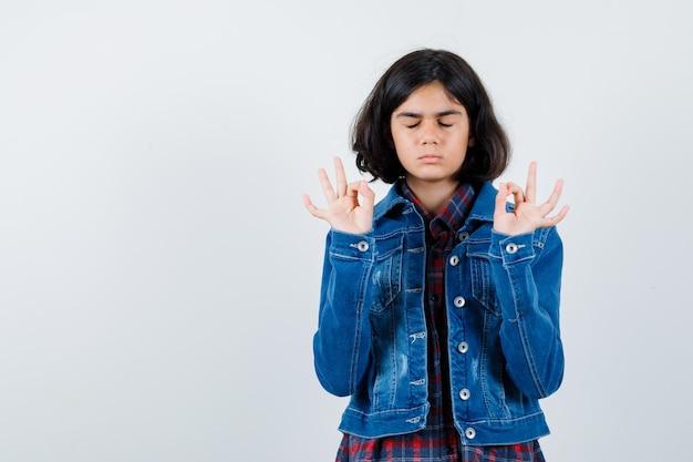 Młoda dziewczyna w kraciastej koszuli i dżinsowej kurtce, medytując i patrząc na spokój, widok z przodu.