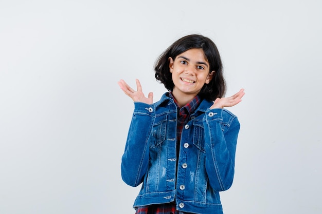 Młoda dziewczyna w kraciastej koszuli i dżinsowej kurtce, rozciągając ręce w sposób przesłuchania i wyglądający ładnie, widok z przodu.