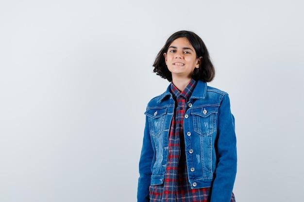 Młoda dziewczyna w kraciastej koszuli i dżinsowej kurtce stojący prosto i pozowanie na aparat i patrząc szczęśliwy, widok z przodu.