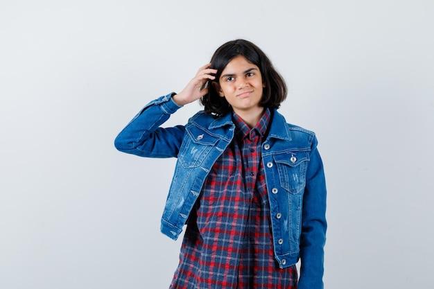 Młoda dziewczyna w kraciastej koszuli i kurtce dżinsowej, drapiąc się po głowie i patrząc szczęśliwy, widok z przodu.