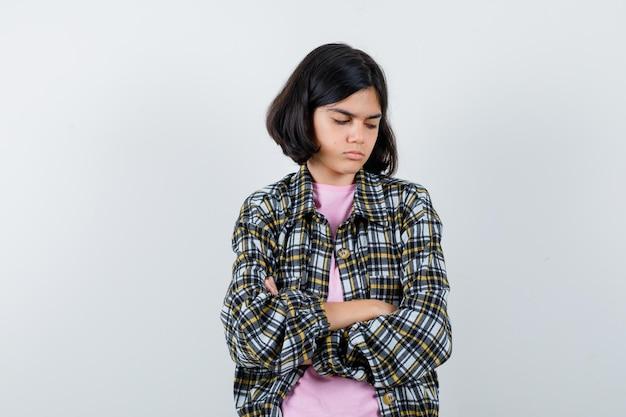 Młoda dziewczyna w kraciastej koszuli i różowej koszulce stojąca ze skrzyżowanymi rękami, patrząca w dół i zamyślona