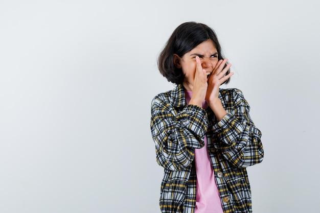 Młoda dziewczyna w kraciastej koszuli i różowej koszulce trzymająca się za ręce przy ustach, gdy dzwoni do kogoś i wygląda zła, widok z przodu.