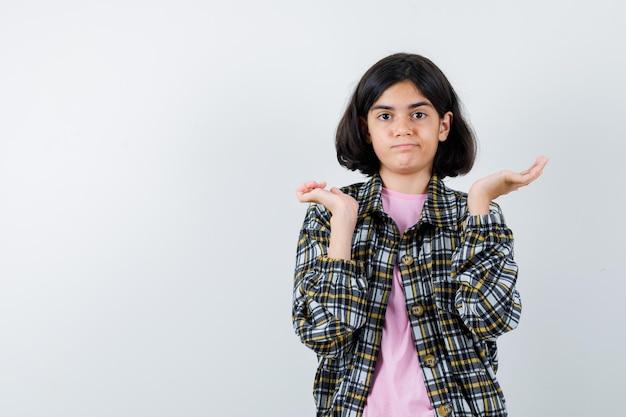 Młoda dziewczyna w kraciastej koszuli i różowej koszulce wyciąga dłonie pytająco i wygląda na zakłopotaną