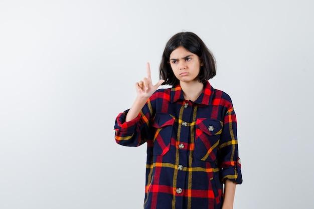 Młoda dziewczyna w kraciastej koszuli pokazuje gest pistoletu i wygląda na wściekłego, widok z przodu.